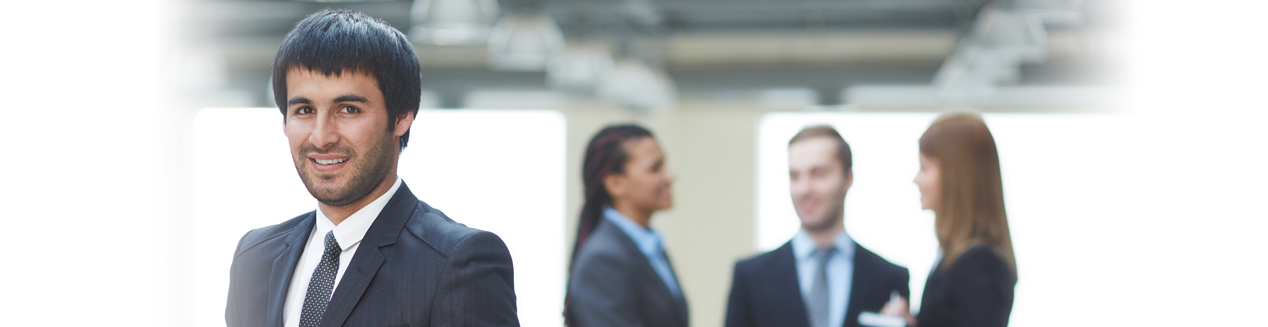 businessman looking at camera with group of business people in background